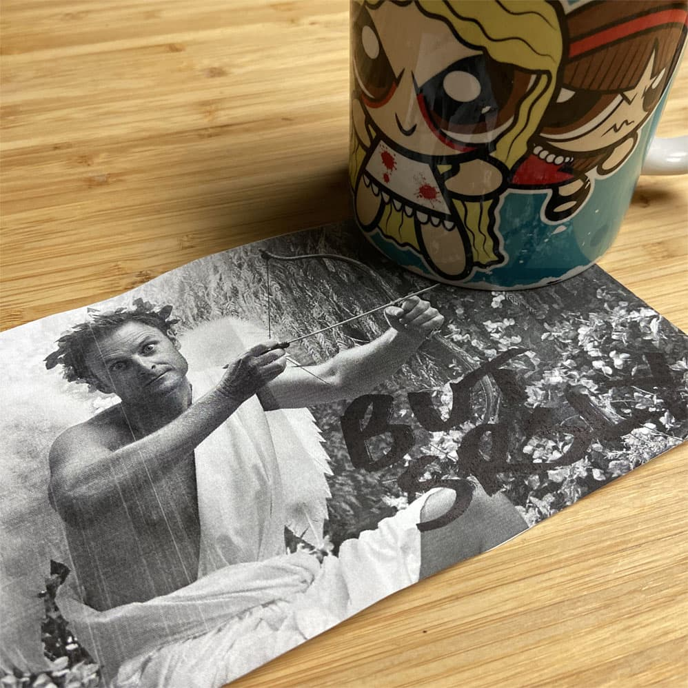 A black and white picture of Chris Harrison, dressed as cupid, with a sharpied note saying 'but srsly?', and a mug with a cartoon version of the characters from Orphan Black