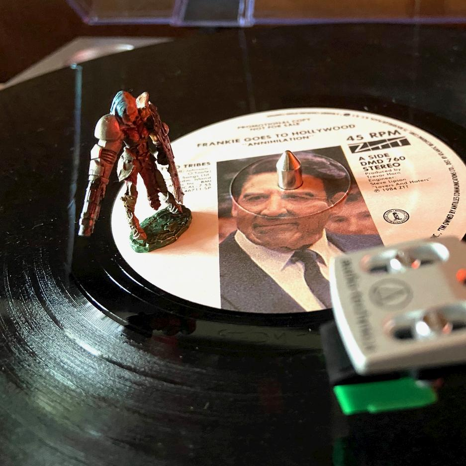A gaming miniature figurine standing on a vinyl record of Frankie Goes to Hollywood's 'Two Tribes'