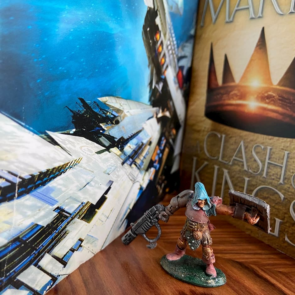 A gaming miniature standing between two books, one fantasy and one sci-fi