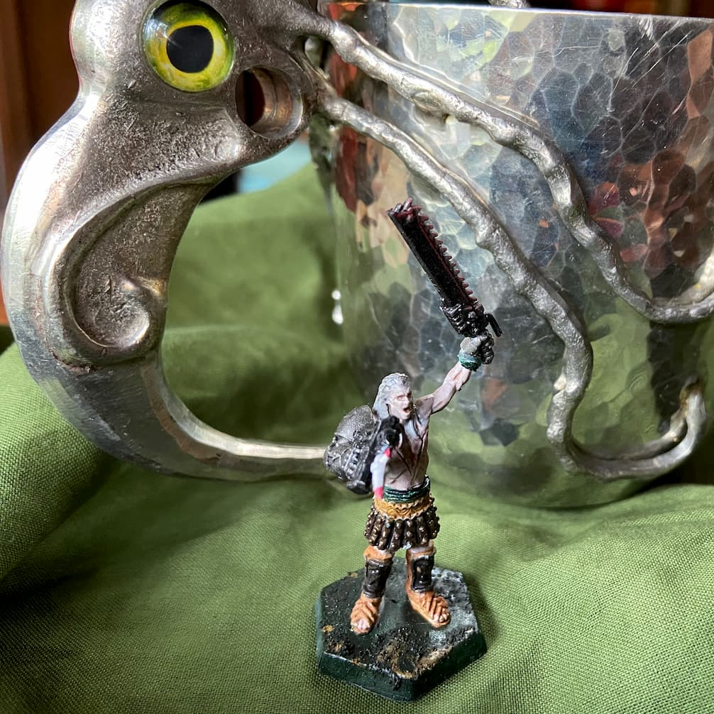 A miniature figure waving a gun and a chainsword, in front of a pewter goblet with a squid shaped handle