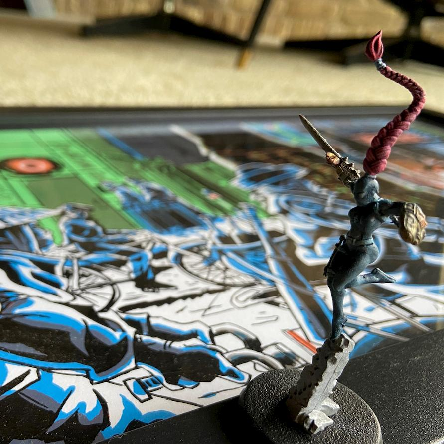 An athletic looking gaming miniature, with pink hair, standing on a Tim Doyle art piece of Blade Runner