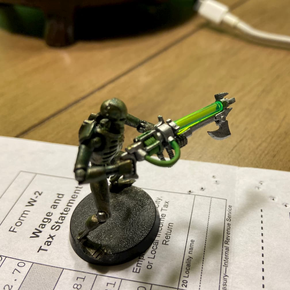 A miniature of a Warhammer 40k Necron standing on a W2 form